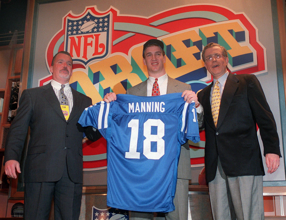. FILE - In this April 18, 1998, file photo, Peyton Manning holds up an Indianapolis Colts jersey as he is flanked by Colts owner Jim Irsay, left, and NFL Commissioner Paul Tagliabue after being chosen as the No. 1 pick in the NFL Draft, in New York. A person with knowledge of the decision tells The Associated Press on Sunday, March 6, 2016, that Manning has informed the Denver Broncos he\'s going to retire. (AP Photo/Adam Nadel, File)