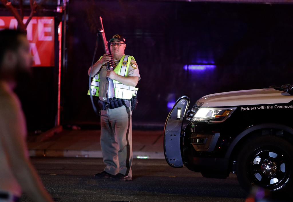 . A police officer stands at the scene of a shooting along the Las Vegas Strip, Monday, Oct. 2, 2017, in Las Vegas. Multiple victims were being transported to hospitals after a shooting late Sunday at a music festival on the Las Vegas Strip. (AP Photo/John Locher)