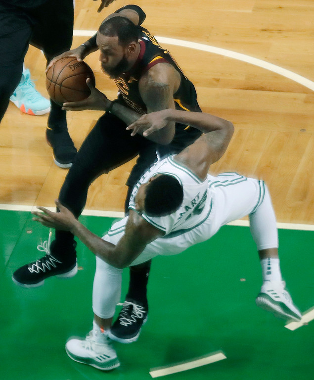 . Cleveland Cavaliers forward LeBron James drives into Boston Celtics guard Marcus Smart, front, during the first half in Game 7 of the NBA basketball Eastern Conference finals, Sunday, May 27, 2018, in Boston. James was charged with an foul. (AP Photo/Charles Krupa)
