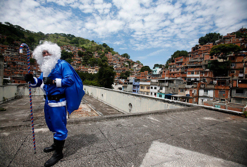 . A policeman of the Peacekeeping Police Unit (UPP) dressed up as Santa Claus in Rio de Janeiro\'s military police colours, arrives for a Christmas party at Macacos slum in Rio de Janeiro December 20, 2012. REUTERS/Ricardo Moraes