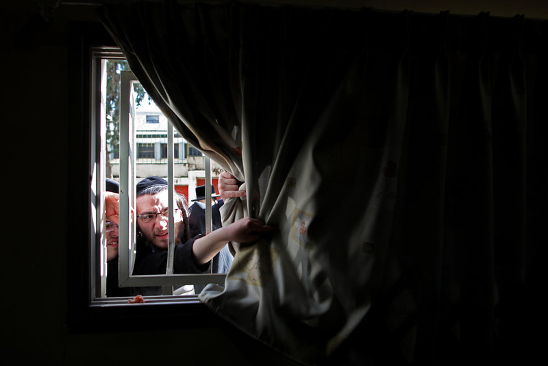 . Ultra-orthodox Jews peek from a window as their Rabbi votes in Bnei Brak, Israel, during legislative elections, Tuesday, Jan. 22, 2013.  Israelis began trickling into polling stations Tuesday morning to cast their votes in a parliamentary election expected to return Prime Minister Benjamin Netanyahu to office despite years of stalled peacemaking with the Palestinians and mounting economic troubles. Polls indicate about a dozen of 32 parties competing in Tuesday\'s election have a chance of winning seats in the 120-member parliament. Most parties fall either into the right-wing-religious or center-left camp, and surveys indicate hard-line and ultra-Orthodox Jewish parties will command a majority. (AP Photo/Oded Balilty)