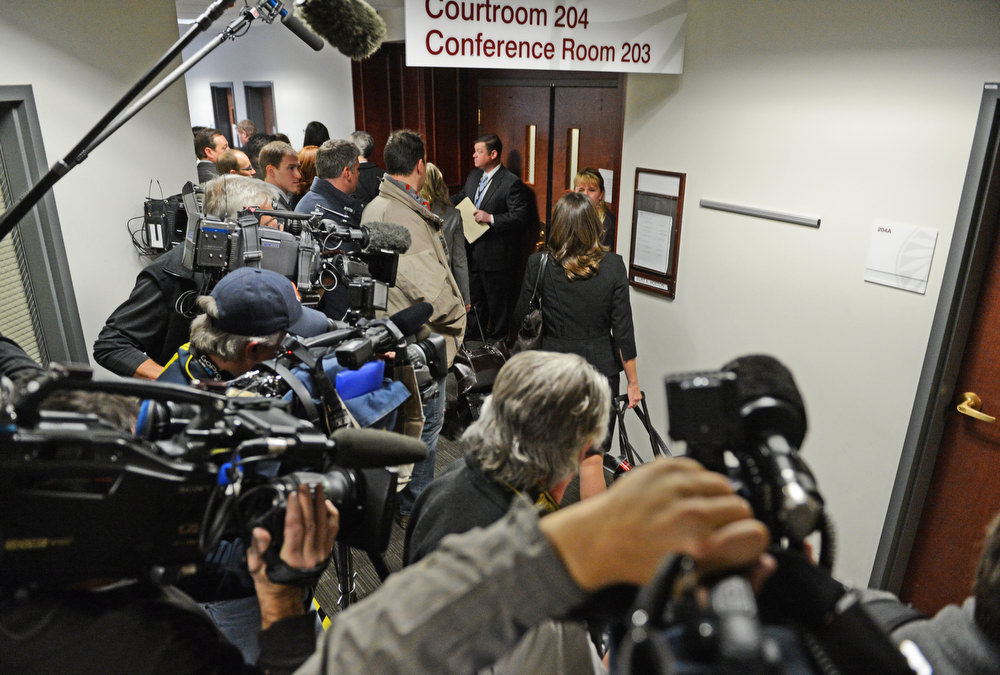 . People head into court, Monday, January 7, 2013, in Centennial pass a wall of media cameras. RJ Sangosti, The Denver Post
