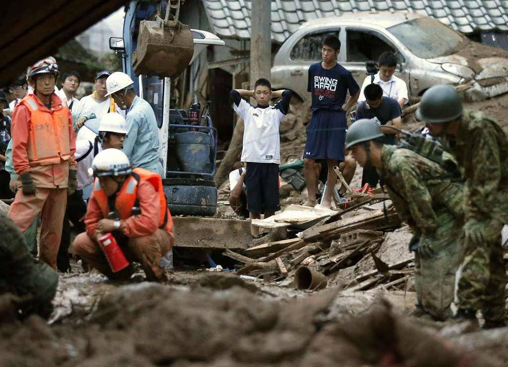 . High school boys watch rescue workers search for their missing classmate after a massive landslide swept through residential areas in Hiroshima, western Japan, Wednesday, Aug. 20, 2014. (AP Photo/Kyodo News)