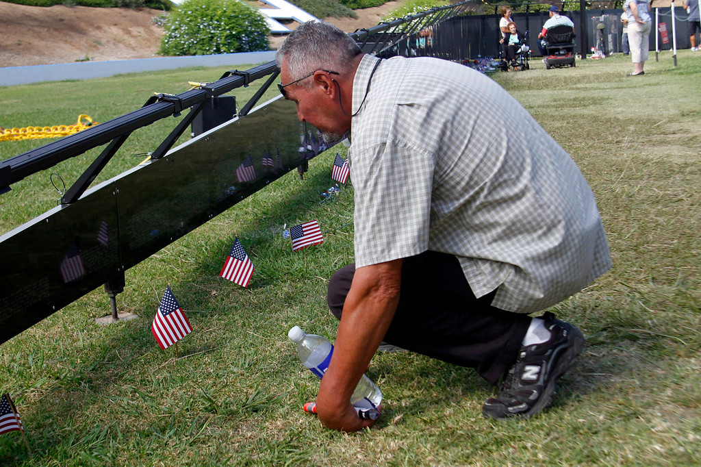 ". Sam Escobar, of La Habra, looks closely for a name on the Vietnam Veterans Memorial, during the Vietnam Veterans Memorial ""The Wall That Heals\"" Closing Ceremony event, at La Habra High School, in La Habra, Sunday, July 14, 2013. (SGVN/Correspondent Photo by James Carbone)"