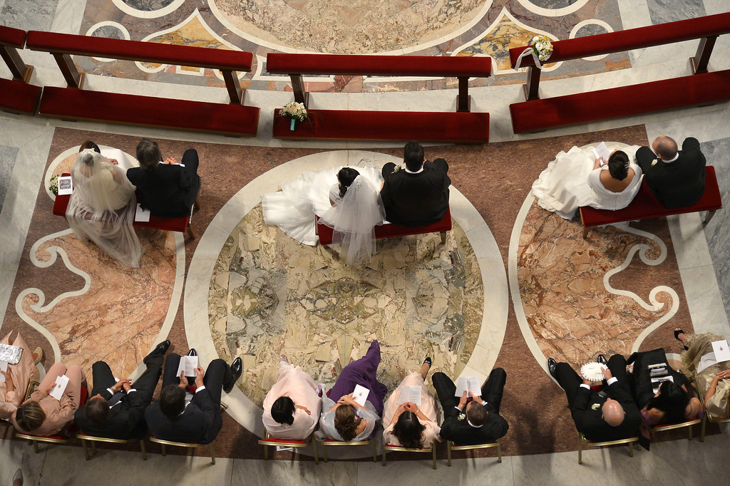 . Wedding couples sit inside St. Peter\'s Basilica as they are married by Pope Francis, at the Vatican, Sunday, Sept. 14, 2014. (AP Photo/Alberto Pizzoli, pool)