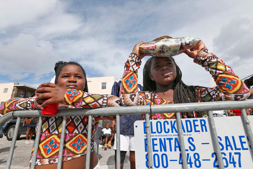 . Twins Toihanna, left, and Marshai Gaiter, 9, watch a parade honoring Martin Luther King Jr., Monday, Jan. 16, 2017, in the Liberty City neighborhood of Miami. (AP Photo/Wilfredo Lee)