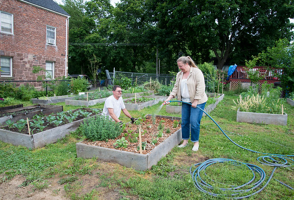 06/24/19 Wesley Bunnell | Staff Rob Runge , L, volunteer with the east side community garden looks over the community herb garden as Chairwoman of the East Side NRZ Julie Swan waters the plants.