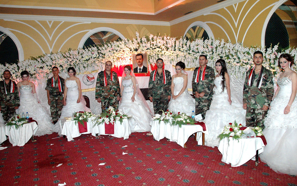 . A handout picture released by the official Syrian Arab News Agency (SANA) on October 11, 2013 shows Syrian soldiers posing with their brides during a mass wedding held in the central Syrian city of Homs. In the center is a portrait of Syrian President Bashar al-Assad.   AFP/Getty Images