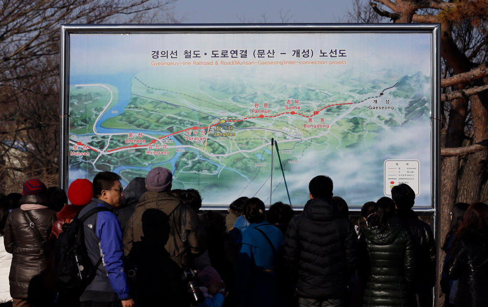 . Tourists look at a map of railroad between two Koreas at the Imjingak Pavilion, near the border village of Panmunjom, which has separated the two Koreas since the Korean War, in Paju, north of Seoul, South Korea, Saturday, Feb. 16, 2013. North Korean defectors and South Korean activists released 200,000 propaganda leaflets across the border to denounce the North Korea\'s third nuclear test and late leader Kim Jong Il\'s birthday on Saturday. (AP Photo/Lee Jin-man)