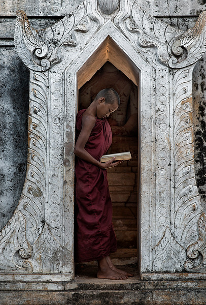 A young monk reads a book whilst a huge stone Buddha keeps an attentive look from within the temple.  Pindaya, Myanmar, 2017