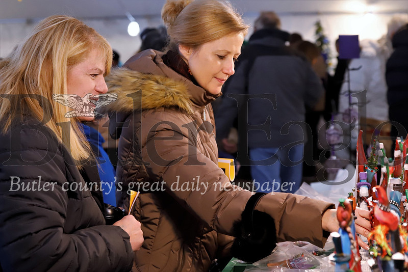 Kelly Kowalski (right) of Penn Township  and Joyce Uranker of Butler shop Tom Niles'  holiday wood carvings display at the Harmony WeihnachtsMarkt christmas market Saturday. Seb Foltz/Butler Eagle