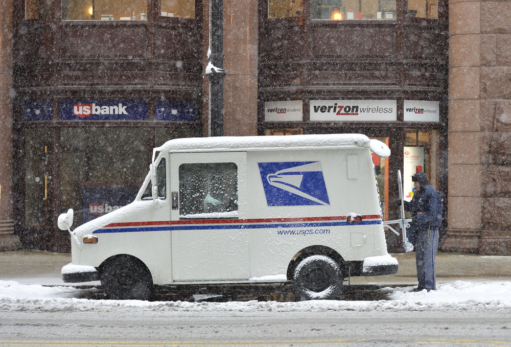 Description of . A mail carrier loads his truck on March 5, 2013 in Chicago, Illinois. The worst winter storm of the season is expected to dump 7-10 inches of snow on the Chicago area with the worst expected for the evening commute.  (Photo by Brian Kersey/Getty Images)