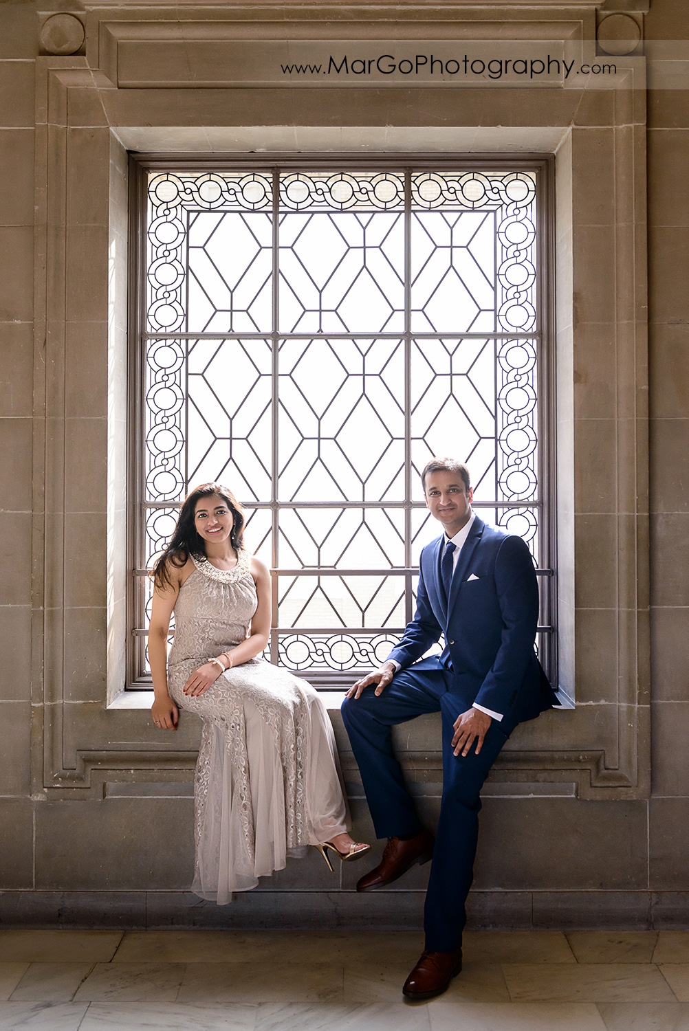 woman in beige dress and man in navy blue suit sitting on the window on the third floor of San Francisco City Hall