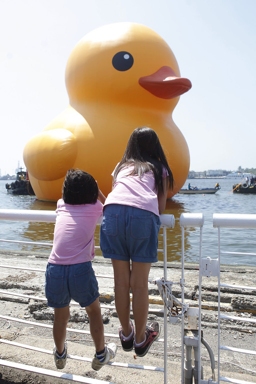 . People gather to see a giant Rubber Duck by Dutch conceptual artist Florentijin Hofman at Glory Pier on September 19, 2013 in Kaohsiung, Taiwan. The \'Rubber\' Duck,\' is traveling the world and will stop in Kaohsiung from September 19 to October 20.  (Photo by Ashley Pon/Getty Images)