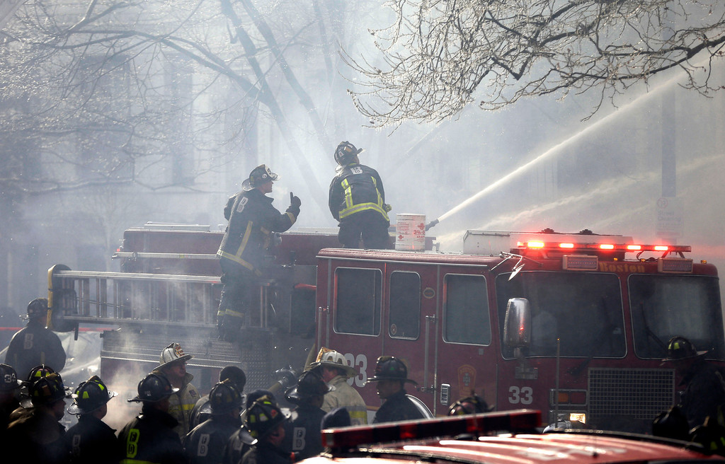 . Fighters battle a multi-alarm fire at a four-story brownstone in the Back Bay neighborhood near the Charles River, Wednesday, March 26, 2014, in Boston.  (AP Photo/Steven Senne)