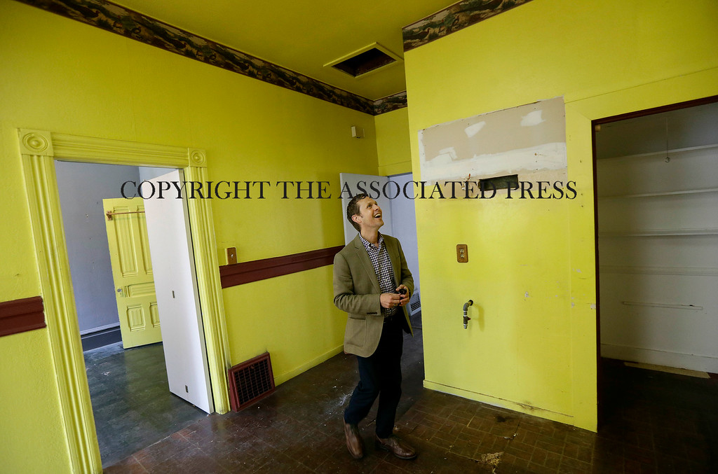 . George Limperis, a realtor with Paragon Real Estate Group, smiles as he walks through the kitchen of a property that was recently sold in the Noe Valley neighborhood in San Francisco, Wednesday, July 30, 2014. (AP Photo/Jeff Chiu)