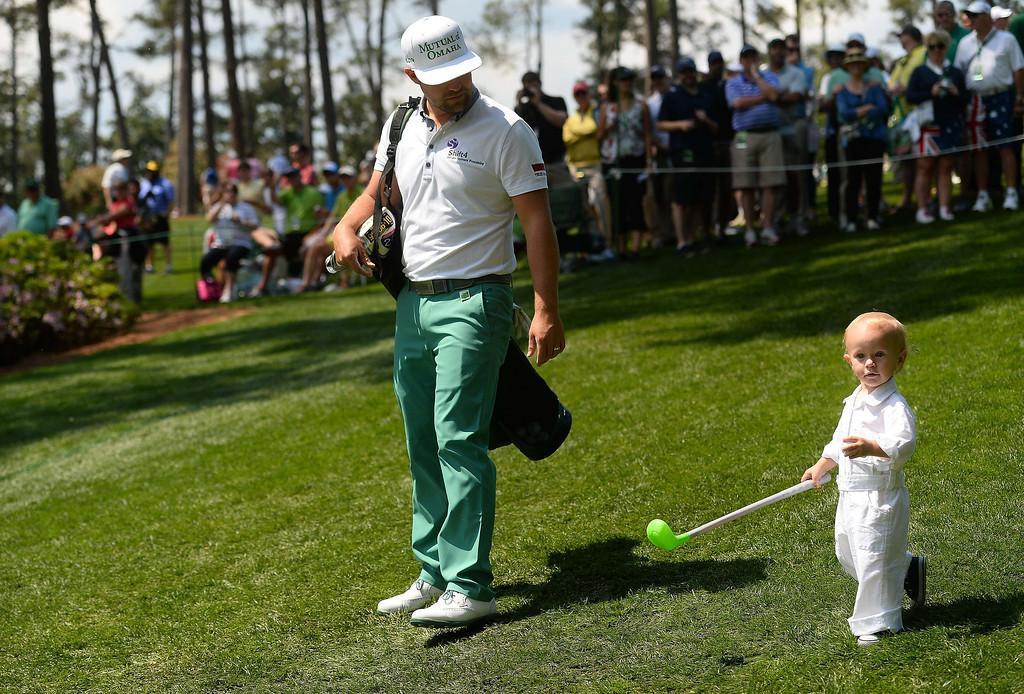 """. US golfer Ryan Moore walks his son tucker as he competes in the Par-3 Contests at the Masters Tournament at Augusta National Golf Club Augusta, Georgia, April 9, 2014.  Moore shot a 6-under 21 to win the event, calling it a \""""perfect practice day.\""""  EMMANUEL DUNAND/AFP/Getty Images"""