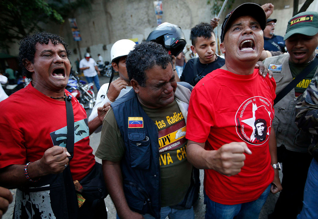 . Supporters of Venezuela\'s President Hugo Chavez react to the announcement of his death in Caracas March 5, 2013. Chavez has died after a two-year battle with cancer, ending the socialist leader\'s 14-year rule of the South American country, Vice President Nicolas Maduro said in a televised speech on Tuesday.    REUTERS/Jorge Silva