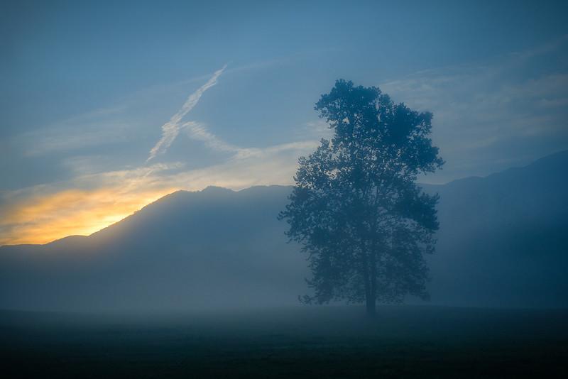 Sun Rising Behind Moutnains on Foggy Morning