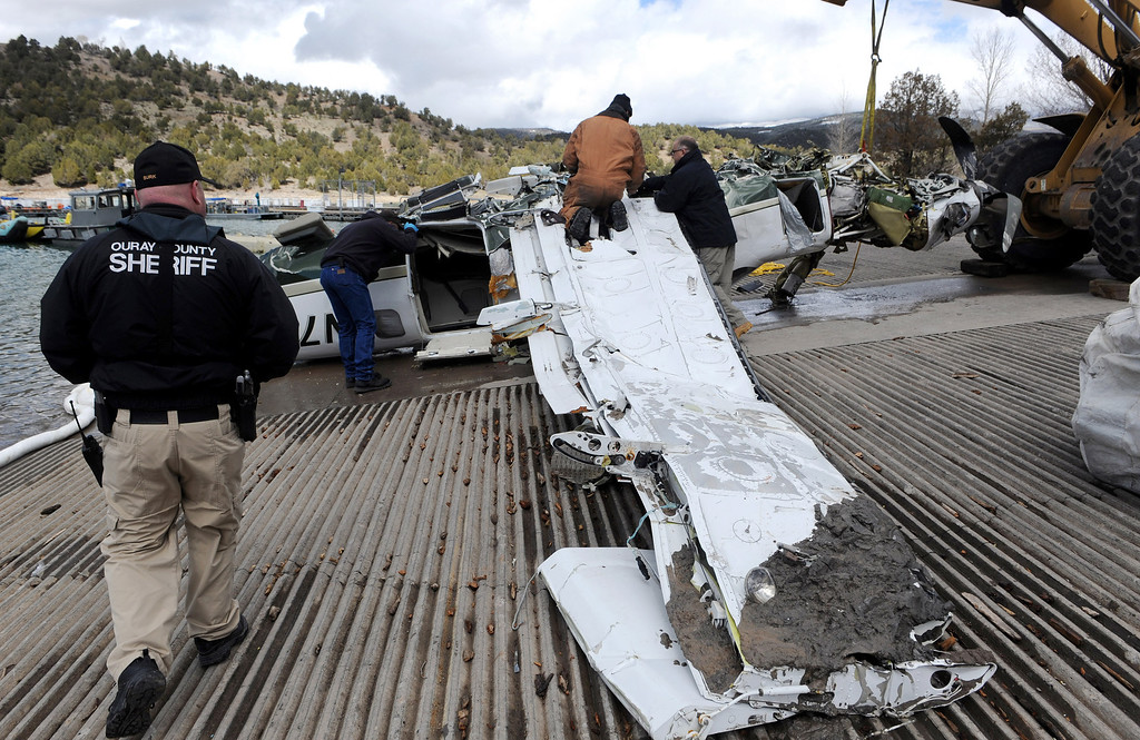 . This photo released by Ouray County shows officials examining the aircraft after it was recovered with the five victims on Thursday March 27, 2014, at the Ridgway Reservoir near Ridgway, Colo.,  The plane crashed last Saturday, March 22, 2014, killing five people from Alabama. (AP Photo/Ouray County, William Woody)