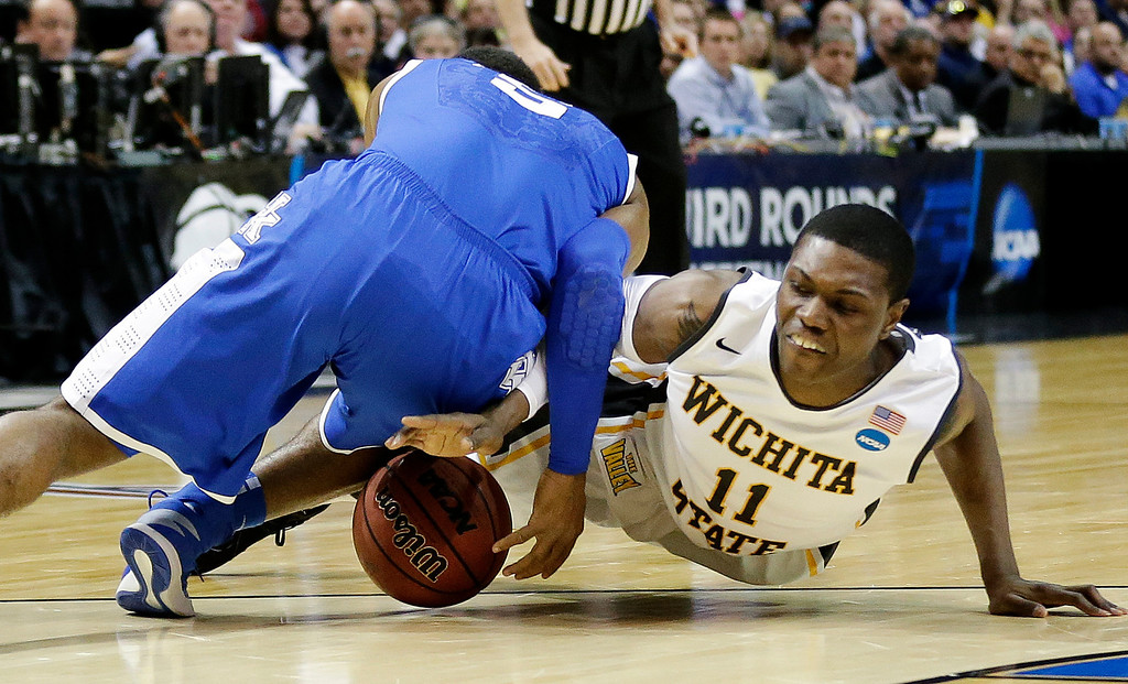. Kentucky guard Andrew Harrison (5) and Wichita State forward Cleanthony Early (11) go after a loose ball during the first half of a third-round game of the NCAA college basketball tournament Sunday, March 23, 2014, in St. Louis. (AP Photo/Charlie Riedel)