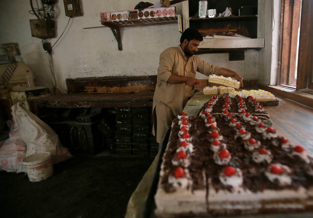 . A Kashmiri baker arranges pastries for sale ahead of Eid al-Fitr in Srinagar, Indian controlled Kashmir Wednesday, June 13, 2018. Eid al-Fitr marks the end of the fasting month of Ramadan. (AP Photo/Mukhtar Khan)