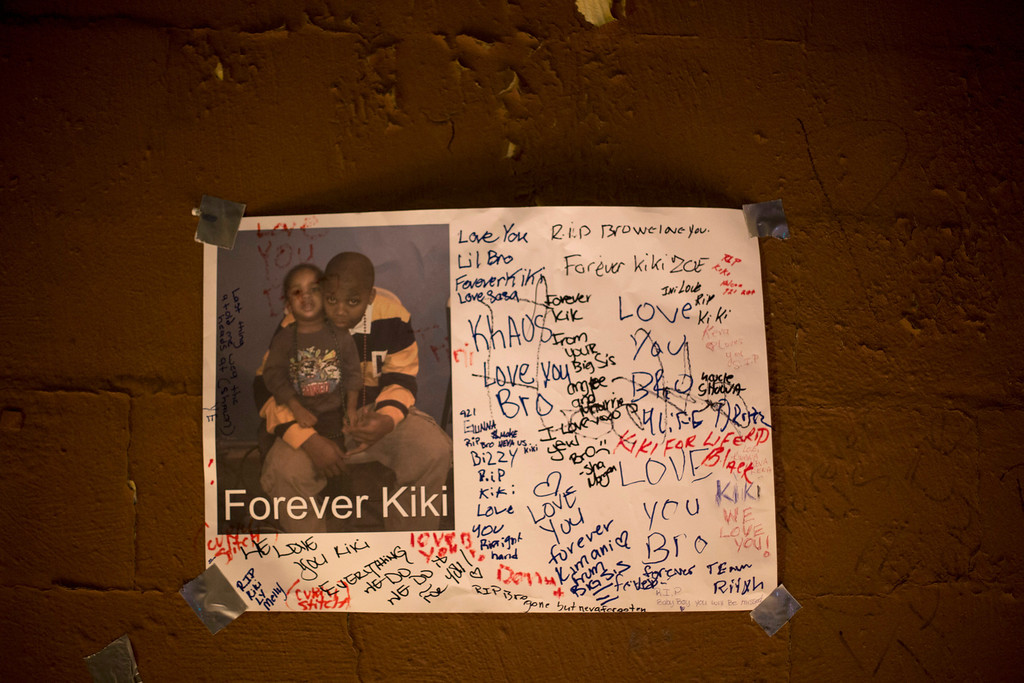 ". A sign with mourners\' notes hangs on a wall above a memorial for 16-year-old Kimani ""Kiki\"" Gray after he was killed in a New York Police Department shooting in the Brooklyn borough of New York, March 11, 2013. Picture taken March 11, 2013.  REUTERS/Lucas Jackson"