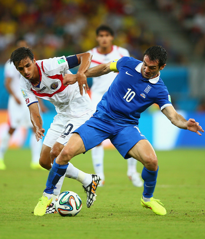 . Bryan Ruiz of Costa Rica challenges Giorgos Karagounis of Greece during the 2014 FIFA World Cup Brazil Round of 16 match between Costa Rica and Greece at Arena Pernambuco on June 29, 2014 in Recife, Brazil.  (Photo by Paul Gilham/Getty Images)