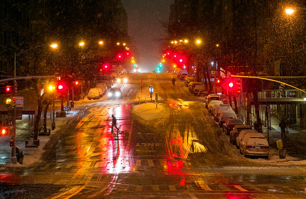 . A person crosses a snow-covered street in the Upper West Side neighborhood of New York, Monday, Jan. 26, 2015. People in the Northeast by the thousands prepared for a snowstorm that could be one for the history books, with some 35 million people in its path in the Philadelphia-to-Boston corridor. (AP Photo/Craig Ruttle)