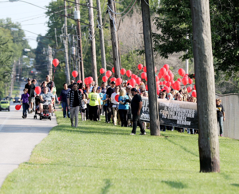 . Jonathan Tressler - The News-Herald. Hundreds of people, possibly a quarter-mile long, proceed north on Fairgrounds Road at teh start of the prayer march/memorial at the start of the two-day Hope Over Heroin Lake County event Aug. 25.
