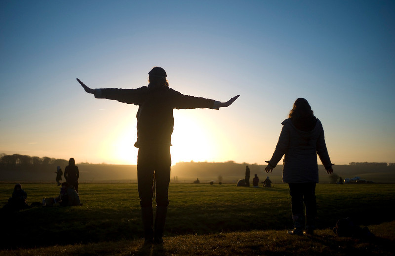 . Revellers chant incantations as the sun rises during the winter solstice at Stonehenge on Salisbury Plain in southern England December 21, 2012. The winter solstice is the shortest day of the year, and the longest night of the year. REUTERS/Kieran Doherty