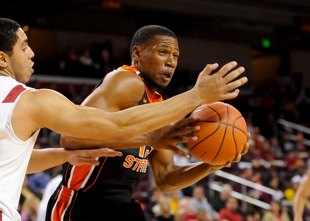 Description of . Oregon State guard Langston Morris-Walker, right, drives on Southern Cal forward Aaron Fuller, left, as he battles to the basket during the first half of an NCAA college basketball game, Saturday, Jan. 19, 2013, in Los Angeles. (AP Photo/Gus Ruelas)