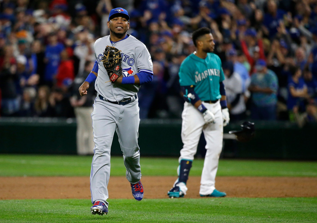 . Toronto Blue Jays first baseman Edwin Encarnacion, left, runs to the dugout after Seattle Mariners\' Robinson Cano, right, lined out to right field with the bases loaded to end the eighth inning of a baseball game, Monday, Sept. 19, 2016, in Seattle. (AP Photo/Ted S. Warren)