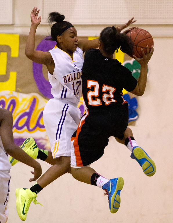 . Oakland Technical High School\'s Elayshia Woolridge (12) challenges McClymonds High School\' Ny\' Dajah Jackson (22) as she drives to the hoop during the fourth quarter of their Oakland Athletic League girls\' basketball game, Wednesday, Feb. 20, 2013 in Oakland, Calif. McClymonds won, 62-50. (D. Ross Cameron/Staff)