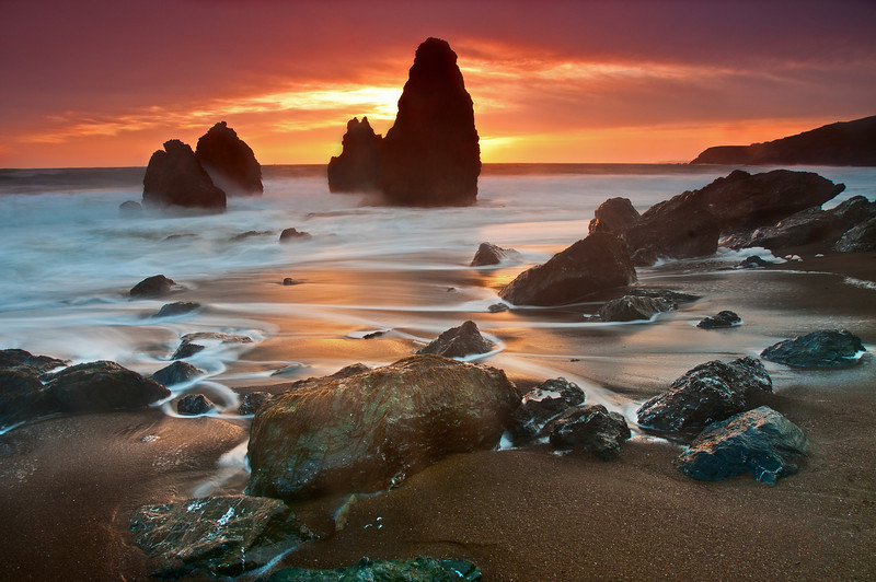 Last week my buddy and I grabbed our cameras, left work a bit early, and drove up to the Marin Headlands to take photos at Rodeo Beach. We knew these rock pillars were here and had seen some great photos of it and wanted to make our go. I've posted a couple other photos from this photoshoot but several of my friends really liked this photo so I had to throw this one up too!  As soon as I threw on the my circular polarizer and the Graduated Filters the sky LIT UP! It was like an explosion of color! These photos are NOT HDR and have had very little saturation edits (in fact, I had to lower the saturation a bit so that you wouldn't think it was fake)! The clouds kept the sun hidden so I didn't have any clipping from a bright sun. The soft graduated filters worked great -- gave me some great color in the sky and let me slow the shutter for some neat wave movements. I'm quite pleased with how these came out!  I've found that the motion of the outgoing wave makes for much nicer photos. I found a nice spot along the beach that wasn't getting too wet and used the rocks to create a line through the photo. I then used the fleeting water to create another line, away from it … trying to draw your eye in and to the right, then back and to the left. The awesome reflection of the sunset off the sand/water made this photo even nicer.  Nikon D300s w/Nikkor 17-35mm f/2.8 ED-IF AF-S: 17mm, f/8, 8 sec, ISO 125, Tripod B+W F-Pro Circular Polarizer + Hitech 0.9 soft Reverse ND grad filter, Hitech 0.6 soft ND grad filter, and Lee FK Filter holder NO HDR. Decreased saturation in some areas (sky), added sharpening and some dodge/burning.
