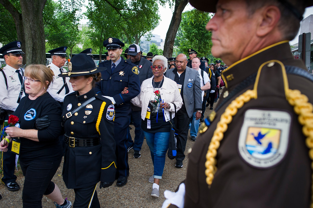 . Family members of police officers killed in the line of duty pass an honor guard as they arrive for the National Law Enforcement Officers Memorial Fund 30th annual Candlelight Vigil, to commemorate new names added to the monument, on the Mall in Washington, Sunday, May 13, 2018. (AP Photo/Cliff Owen)
