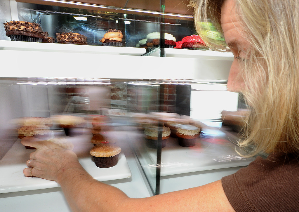 . Co-owner Vany Altounian, reaching for cupcakes for customers as one of the few brave souls in the area to offer the highly sought-after treat at ConfeXi Cupcakes+Cake in Old Pasadena Wednesday August 21, 2013.(SGVN/Photo by Walt Mancini)
