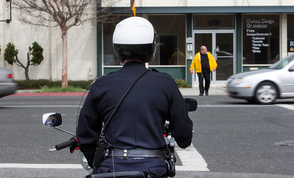 . A motorcycle officer looks for drivers not stopping for pedestrians crossing El Camino Real at Edgewood in Redwood City, Calif., on Wednesday, March 20, 2013. Twenty five offcers from 16 agencies participated in the county wide effort targeting drivers not stopping for pedestrians and excessive speed. About 200 citations were handed out on Wednesday. (John Green/Staff)