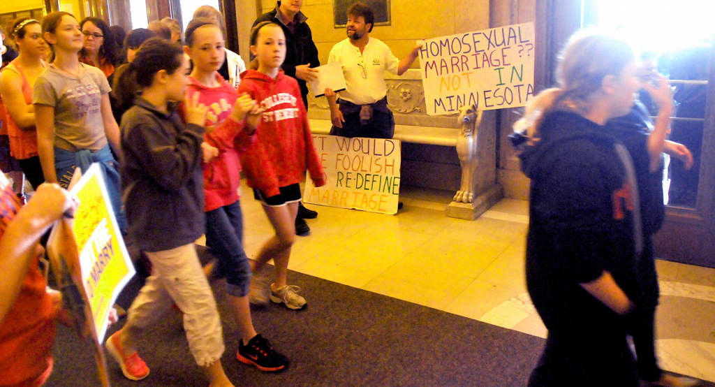 . Patrick Dolney of Apple Valley displays his handmade posters against gay marriage as school groups pass by before the House floor vote. (Pioneer Press: John Doman)