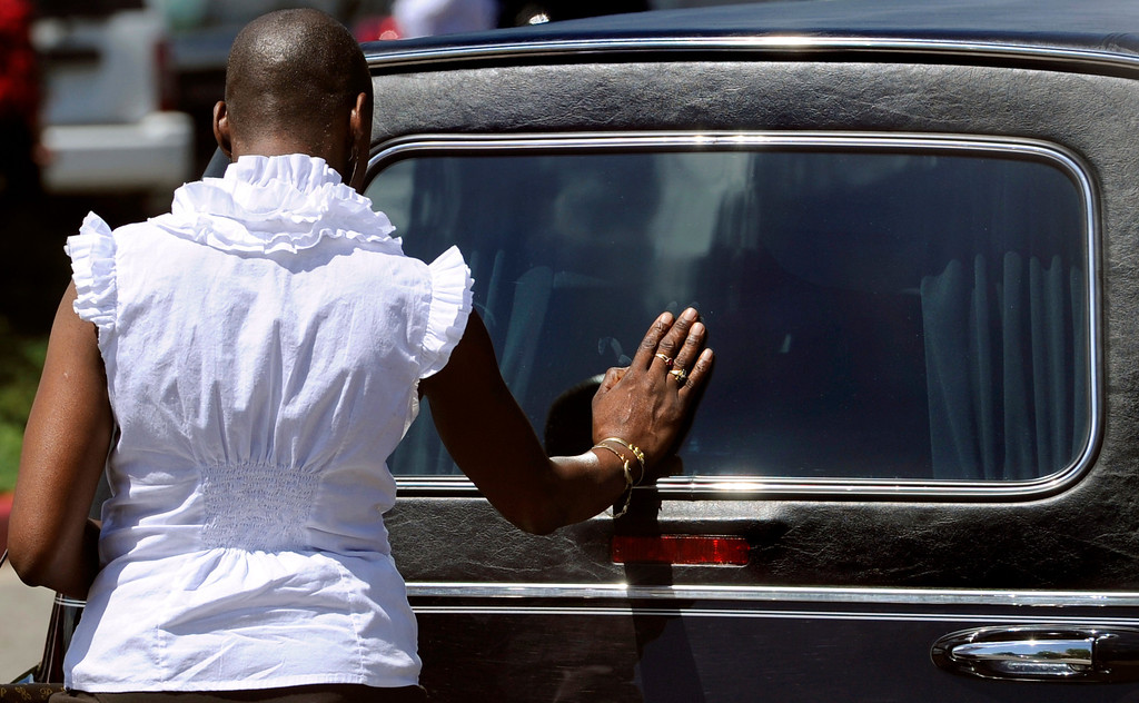 . With the casket of AJ Boik already placed inside, a woman pauses and places her hand on the back window of the hearse. Funeral services for AJ Boik were held on Friday, July 27, 2012 at Queen of Peace Catholic Church in Aurora. Boik was one of twelve victims who died in the theater shooting in Aurora. Kathryn Scott Osler, The Denver Post