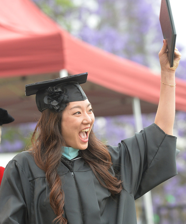 . Jinny Shim shows her diploma to a cheering family during the Commencement Ceremony at Biola University in La Mirada on Friday May 23, 2014. Kay Warren, International speaker and author, gives the commencement address. (Photo by Keith Durflinger/Whittier Daily News)