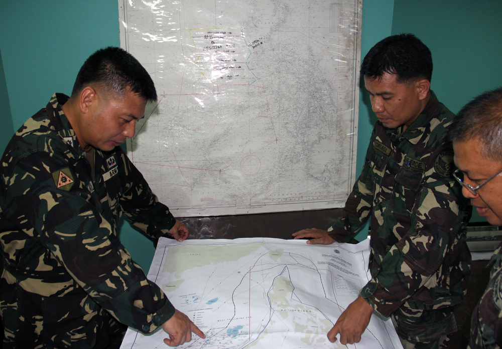 . This handout photo released by the Philippine Military Western Command shows personnel planning search and rescue operations for a missing Malaysia Airlines plane at Antonio Bautista Air Base in Puerto Princesa in the Philippines on March 8, 2014. Rescuers from several nations mounted an air and sea search on March 8 for a Malaysia Airlines jet that has gone missing over Southeast Asia, with grave fears for the 239 people on board. (AFP PHOTO / PHILIPPINE MILITARY WESTERN COMMAND)