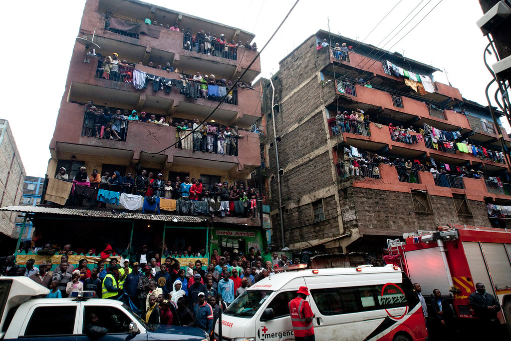 . People view a collapsed building and an ambulance and a fire brigade engine are on on standby as rescue workers remove stones at the site of a building collapse in Nairobi, Kenya, Saturday, April 30, 2016. (AP Photo/Sayyid Abdul Azim)