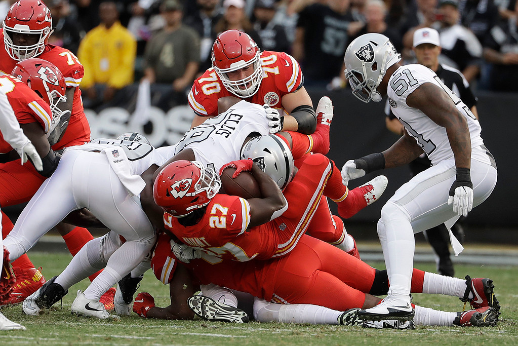 . Kansas City Chiefs running back Kareem Hunt (27) is tackled against the Oakland Raiders during the first half of an NFL football game in Oakland, Calif., Thursday, Oct. 19, 2017. (AP Photo/Marcio Jose Sanchez)