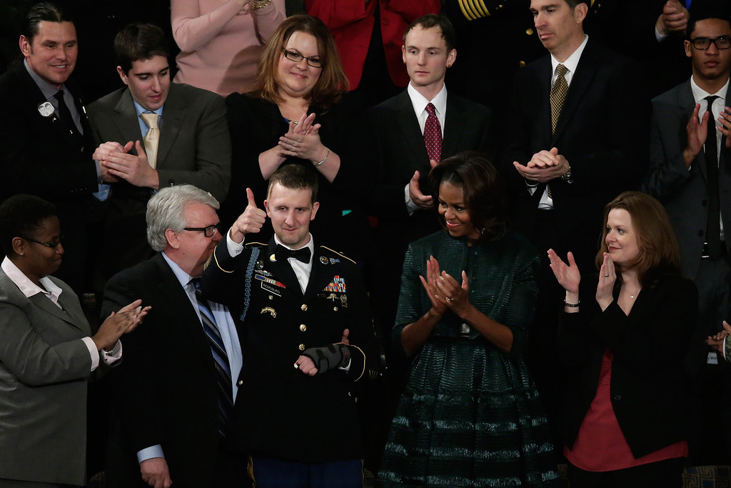 . WASHINGTON, DC - JANUARY 28:  First lady Michelle Obama (R) applauds as US Army Ranger Sergeant First Class Cory Remsburg is acknowledged by U.S. President Barack Obama during the State of the Union address to a joint session of Congress in the House Chamber at the U.S. Capitol on January 28, 2014 in Washington, DC. In his fifth State of the Union address, Obama is expected to emphasize on healthcare, economic fairness and new initiatives designed to stimulate the U.S. economy with bipartisan cooperation.  (Photo by Win McNamee/Getty Images)