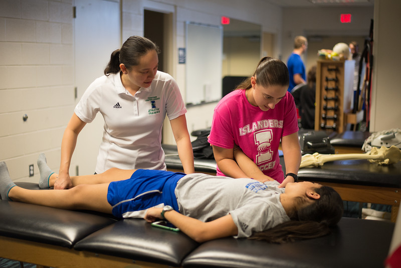 Clinical professor Sayuri Hiraishi observes student Amanda Clark as she demonstrates a shoulder analysis on fellow student Kimberly Montez.