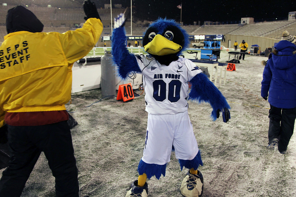 . The Bird, the mascot of Air Force, greets a field guard bundled up against temperatures in the single digits while a light snow envelops Falcon Stadium before Air Force hosts UNLV in the first quarter of an NCAA football game at Air Force Academy, Colo., on Thursday, Nov. 21, 2013. (AP Photo/David Zalubowski)