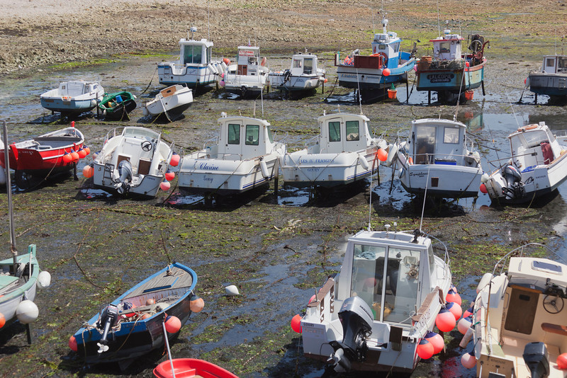 Goury, France - July 3, 2011: Fishing and recreational boats at low tide in the harbor of Goury, France. Goury is a picturesque fishing village at Cap de la Hague on peninsula Cotentin in Basse Normandy.