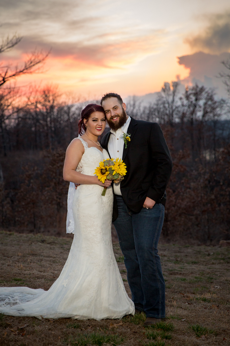 a newlywed couple posing for a photo at sunset after their wedding ceremony