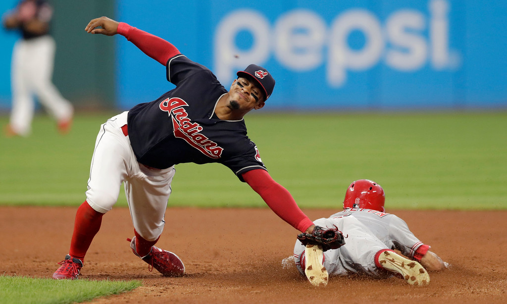. Cleveland Indians\' Francisco Lindor, reaches but can\'t get to a ball thrown by catcher Yan Gomes as Cincinnati Reds\' Billy Hamilton slides safely to second base on a steal in the seventh inning of a baseball game, Monday, July 9, 2018, in Cleveland. Hamilton advanced to third base on a throwing error by Gomes. (AP Photo/Tony Dejak)